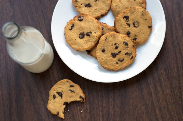 keto cookies on a white plate sitting next to a jug of milk and a half eaten keto cookie