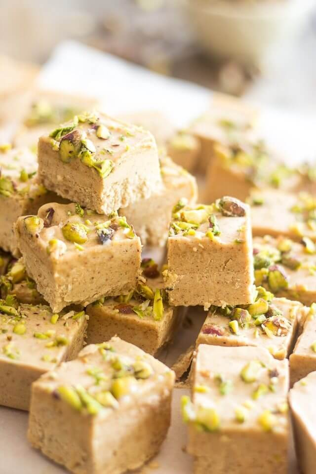 a stack of squares of fat bombs with pistachios on top