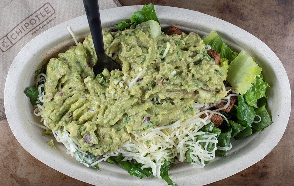 keto chipotle bowl covered with guacamole and a black fork sticking out of the top of the food