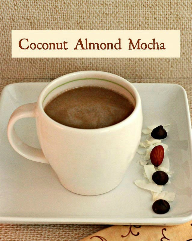 white coffee cup containing coffee flavored almond mocha next to almonds