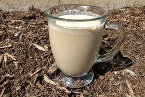 keto coffee in a coffee glass sitting on mulch
