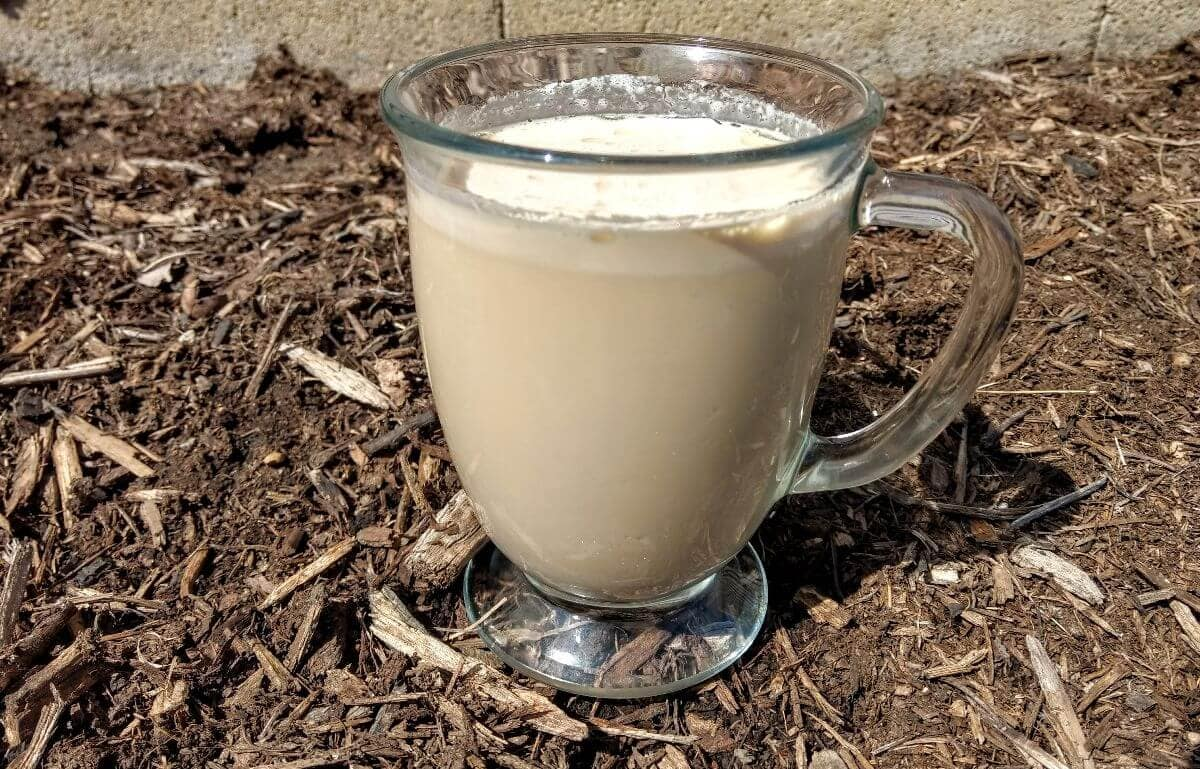 keto coffee in a coffee glass sitting on mulch
