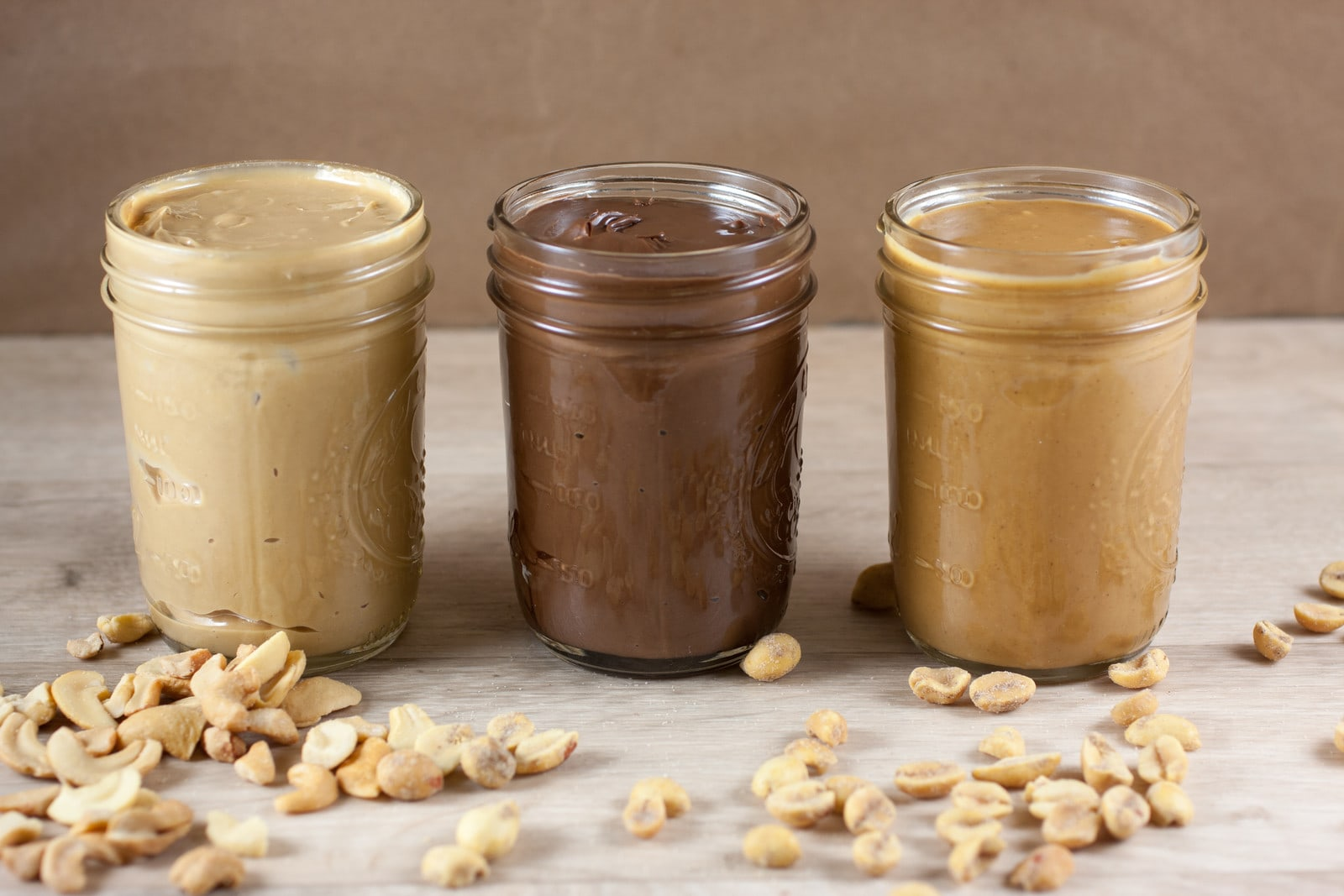 three jars of keto nut butter lined up in a row next to peanuts