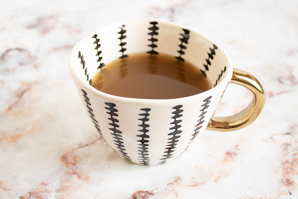 closeup of keto bone broth in cup with gold handle