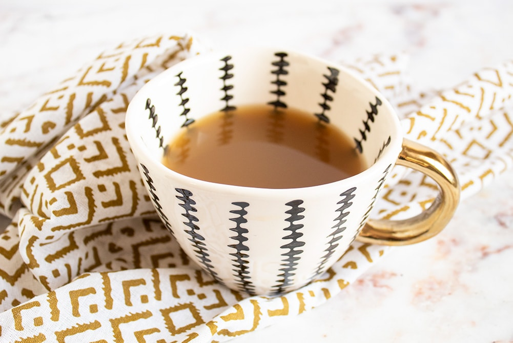 keto bone broth in a striped cup with a gold handle on a gold napkin