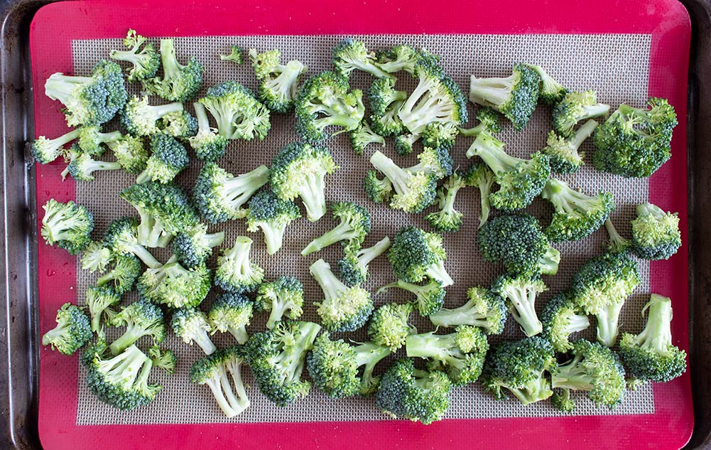 raw broccoli spread on cookie sheet for sheet pan butter burgers