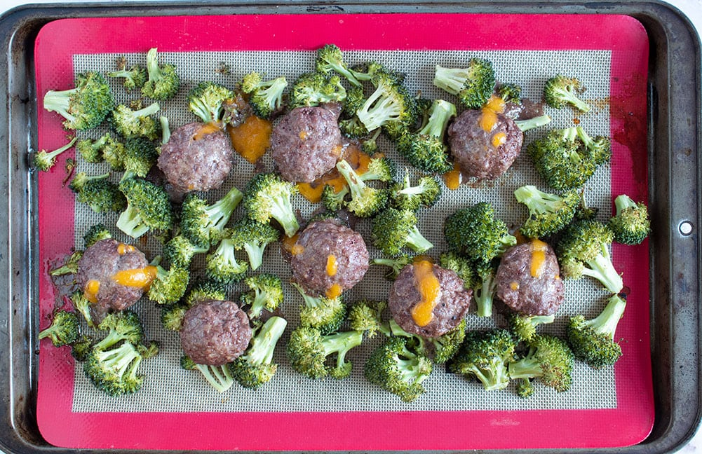 sheet pan butter burgers fully cooked on broccoli