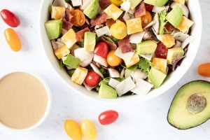 closeup of loaded keto salad surrounded by tahini and avocado