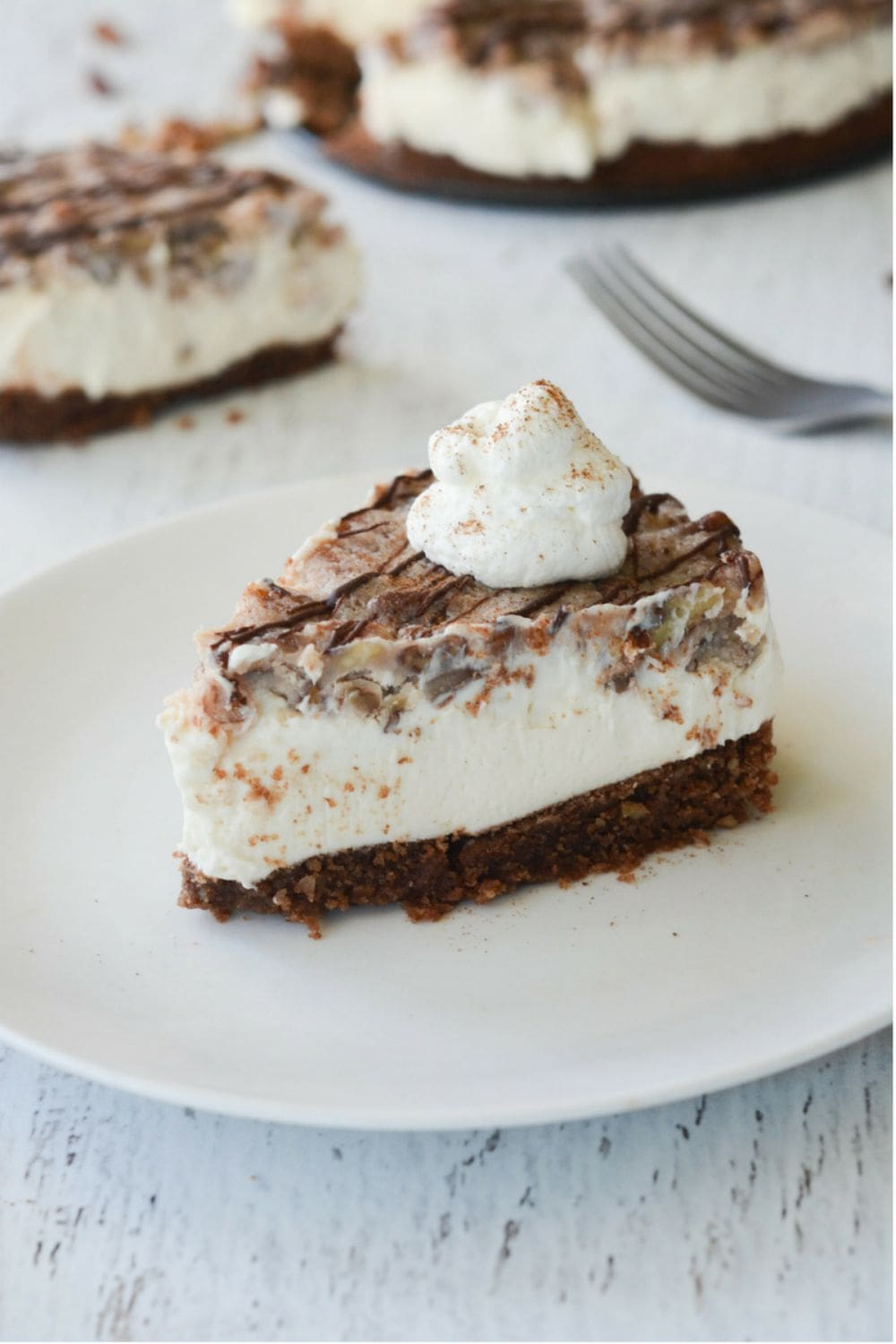 slice of pecan pie keto cheesecake sitting on a dish with pecans and whipped cream topping