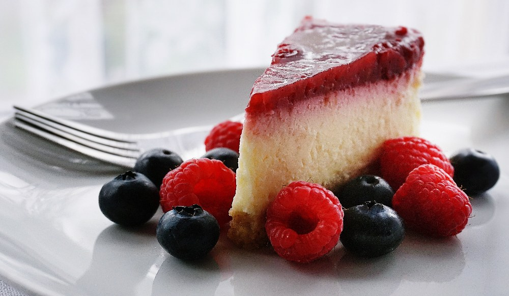 slice of keto cheesecake on a grey plate surrounded by blueberries and raspberries