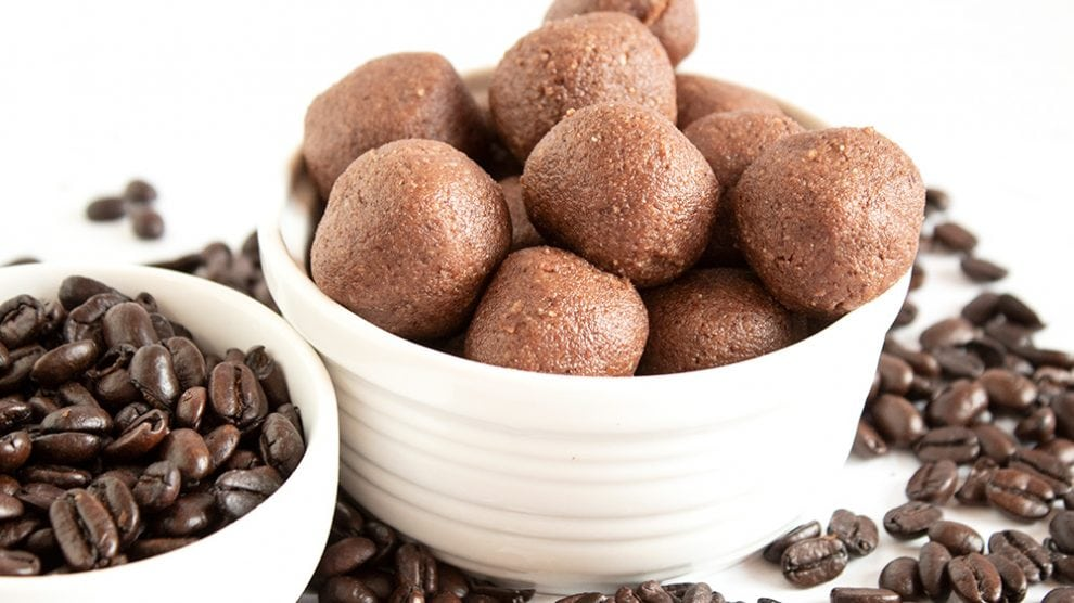 keto chocolate coffee fat bombs in a white dish next to dish of coffee beans