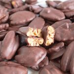 closeup of chocolate covered pecans with several broken in half
