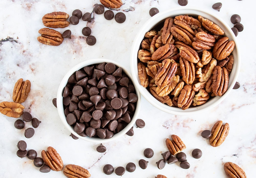 overhead view of ingredients used for chocolate-covered pecans in white bowls