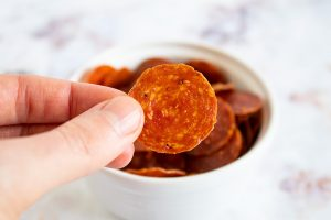 fingers holding up keto pepperoni chips in front of a bowl
