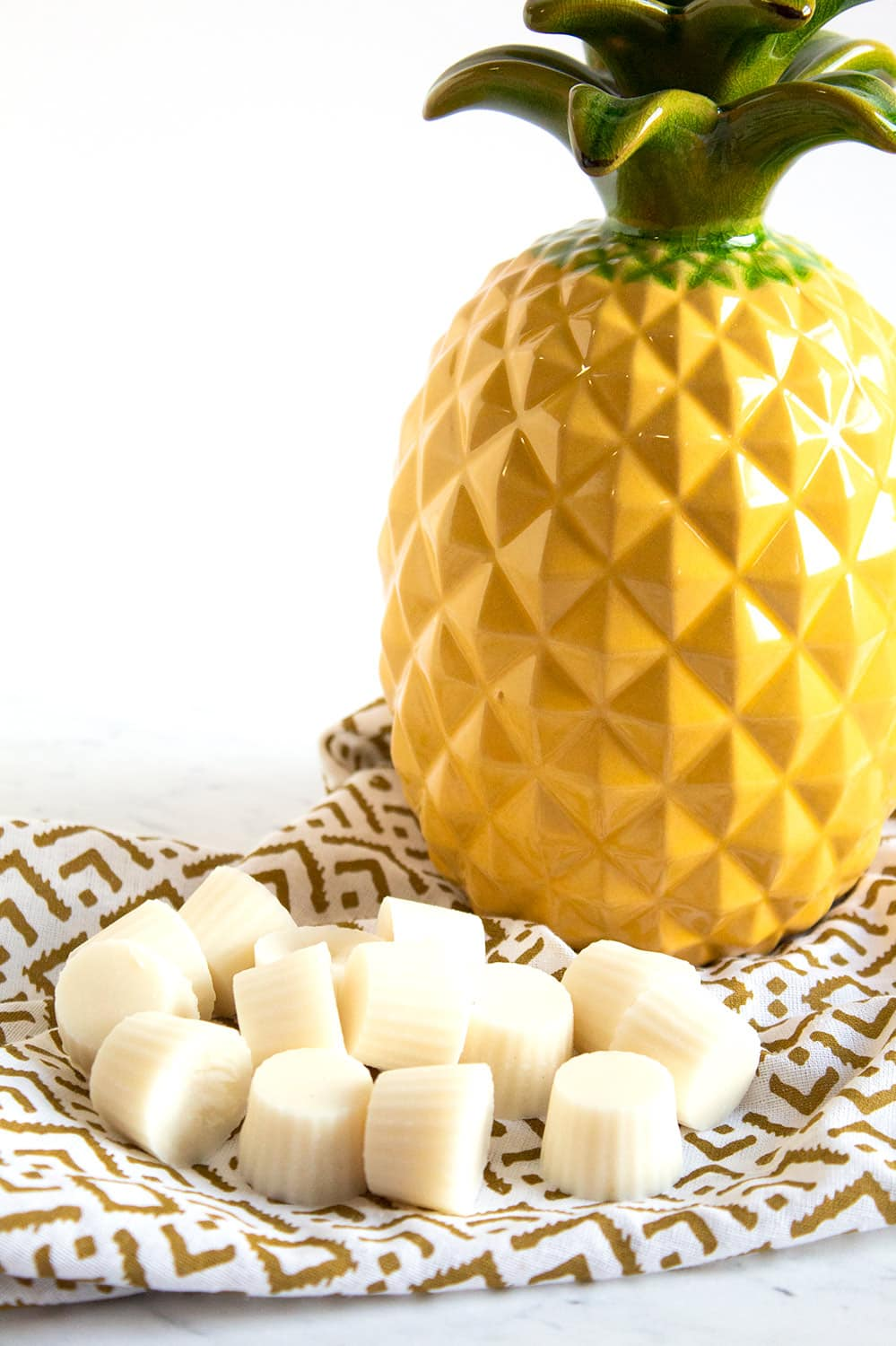 large pineapple sitting next to keto fat bombs on a gold and white towel