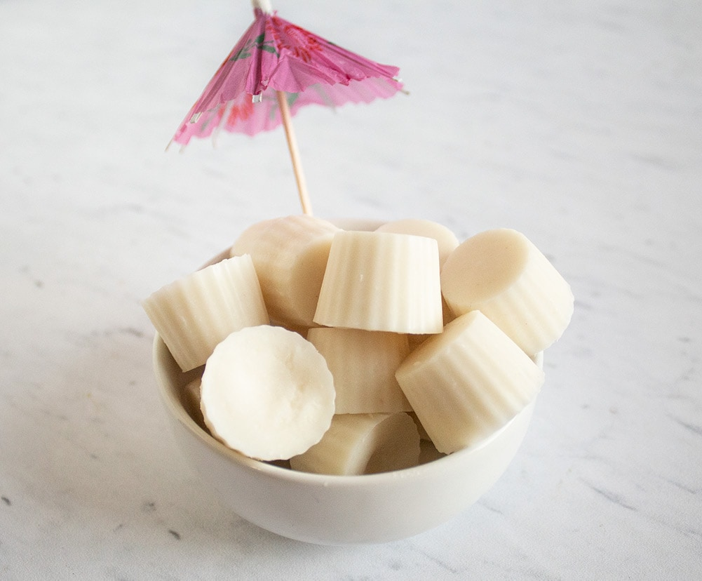 pina colada keto fat bombs in a white bowl with a pink umbrella sticking out