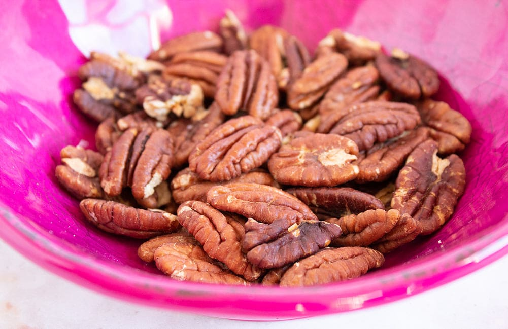 keto butter pecans in a pink bowl toasted