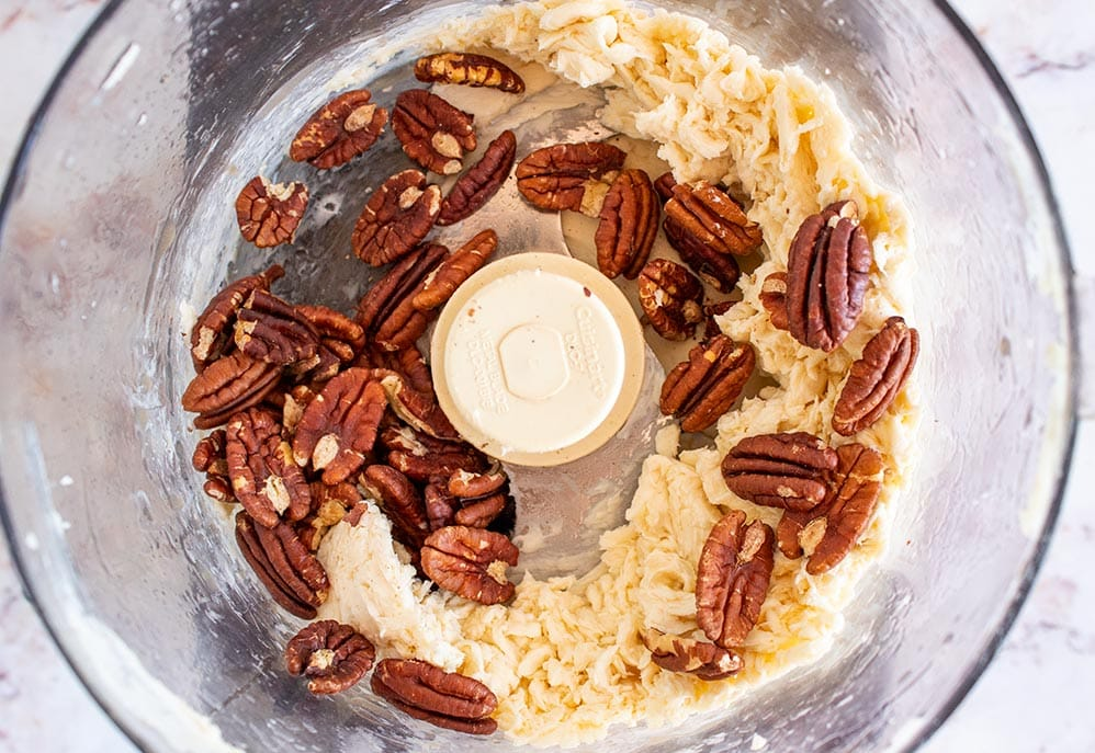 keto butter mixed with toasted pecans inside a food processor bowl
