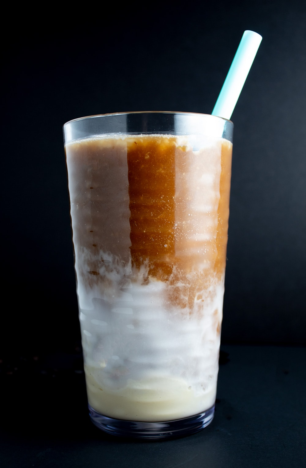 iced coffee closeup of glass with blue straw