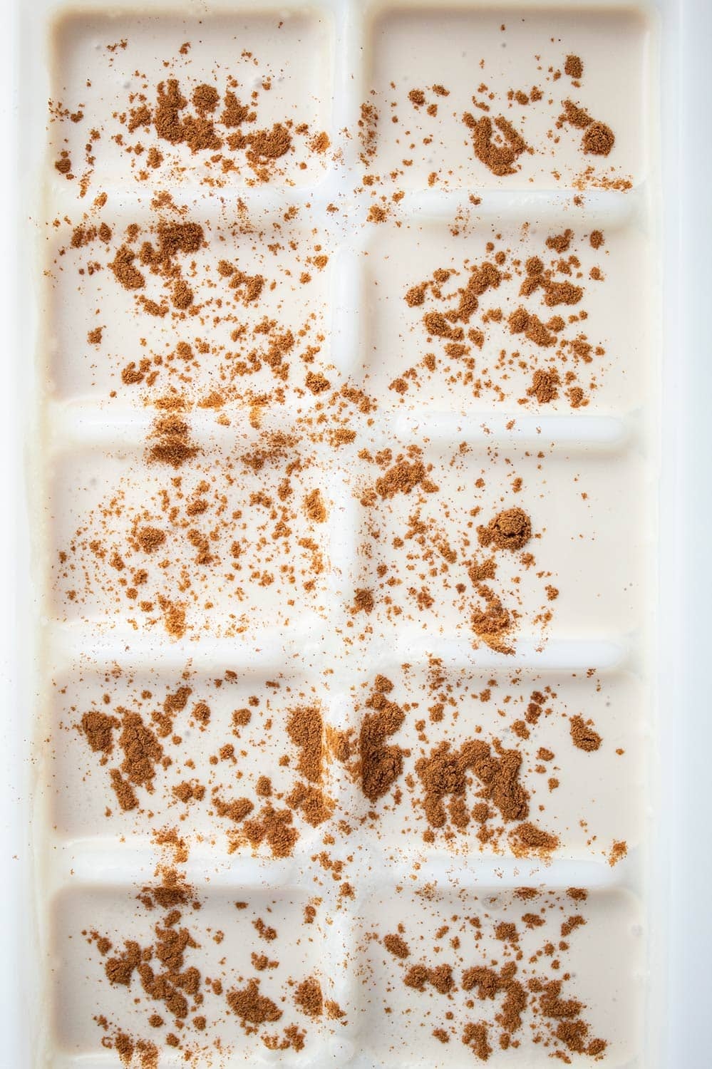 keto iced coffee ice cubes in a tray with cinnamon on top