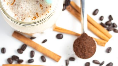 closeup of keto iced coffee top with cinnamon sticks and coffee grounds in background