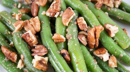 closeup of maple pecan green beans with pecans on top