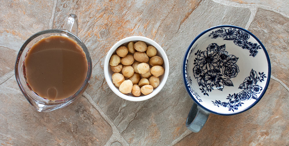 overhead view of ingredients used in macadamia nut fat bomb coffee including coffee in a measuring cup and raw macadamia nuts in a white bowl