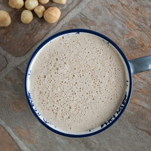 overhead view of blue coffee cup containing macadamia nut coffee with a few macadamia nuts in the corner