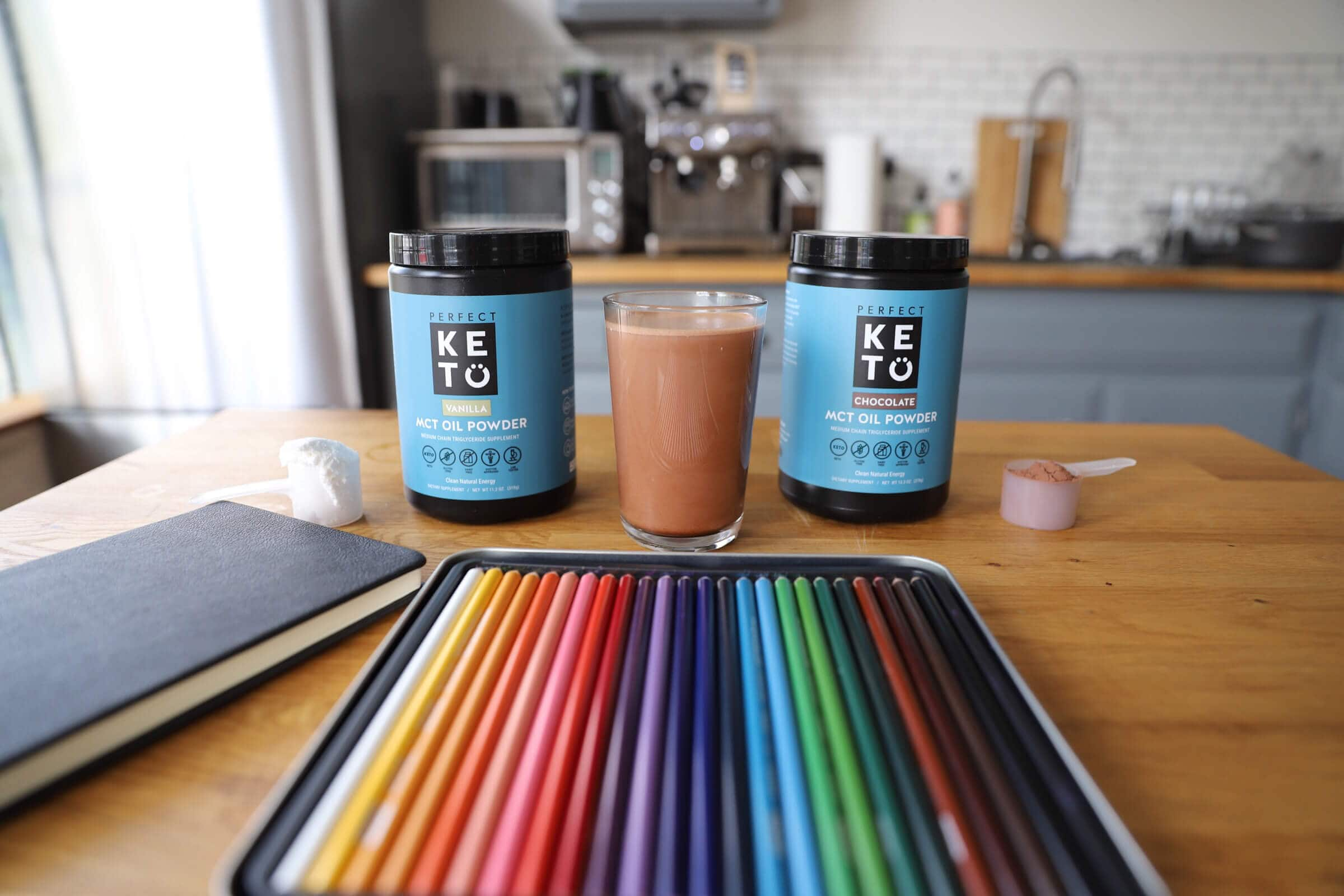 mct oil powder in containers on a kitchen table next to colored pencils