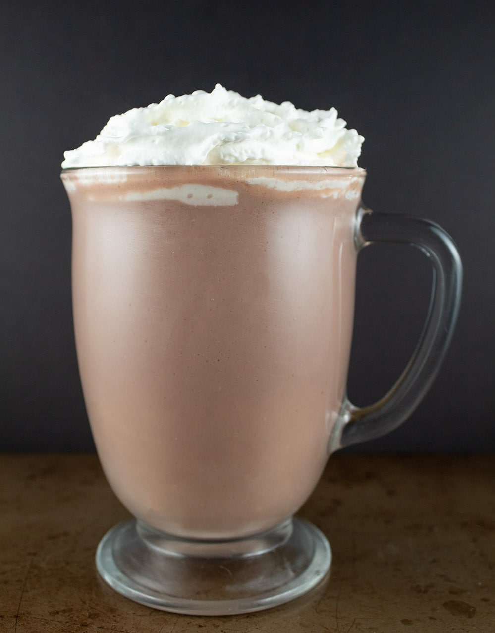 buttery hot chocolate with whipped cream on top in front of a black background