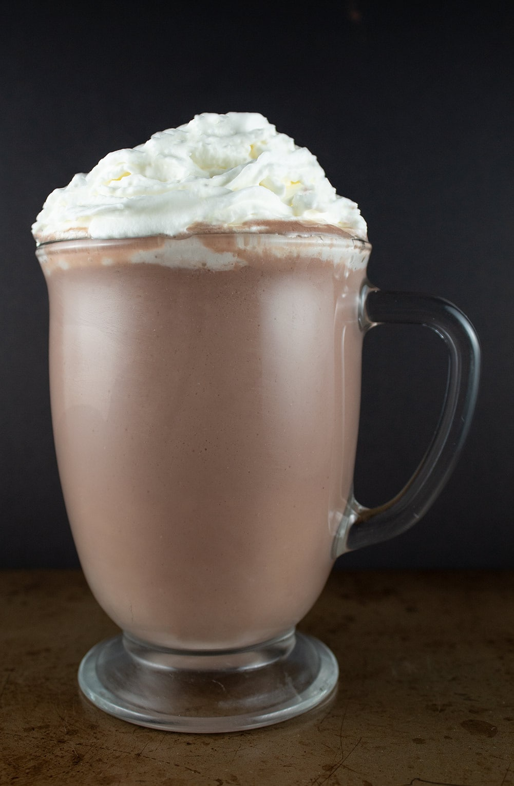 keto hot chocolate against a black background with a ton of whipped cream on top