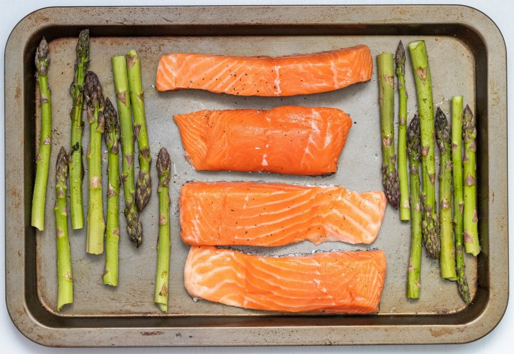 keto on a budget with overhead view of four salmon steaks next to asparagus on a sheet pan