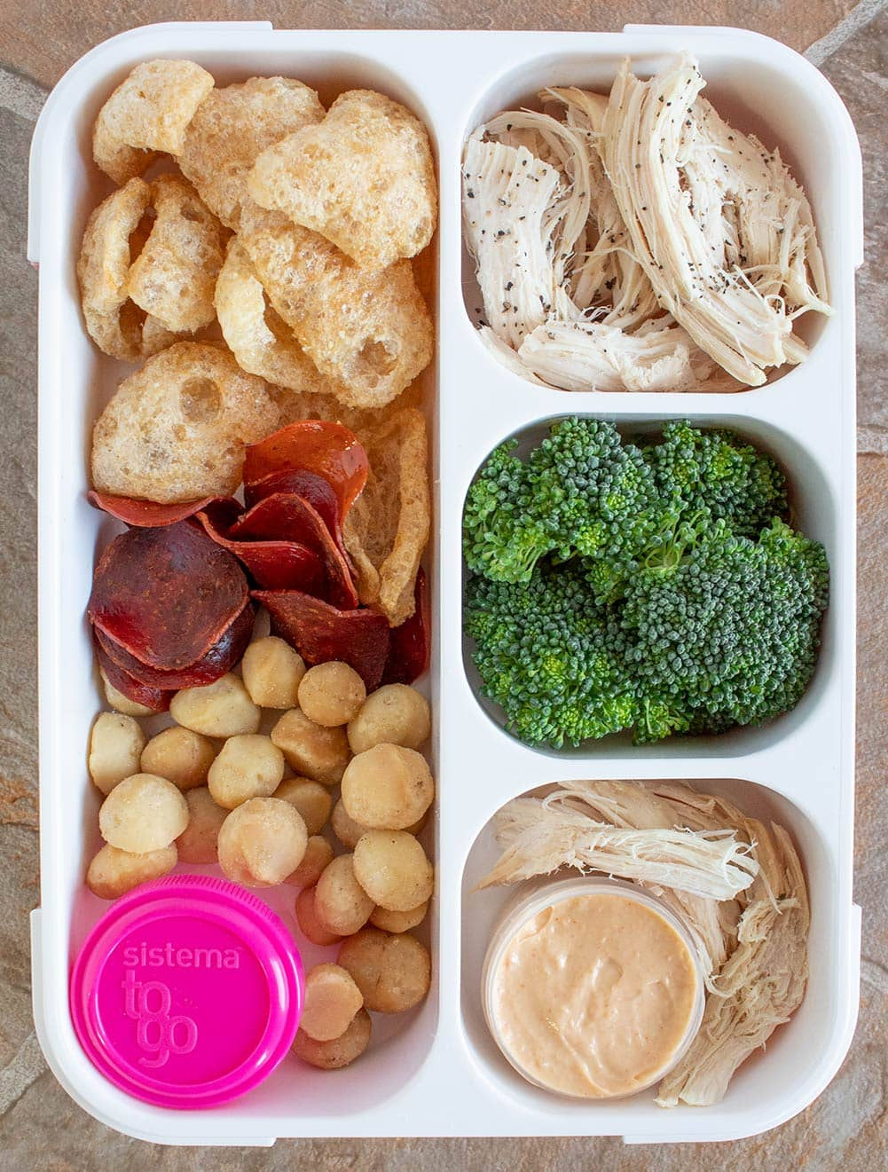 keto starbucks bistro box overhead view with four compartments and a variety of fresh vegetables and meats