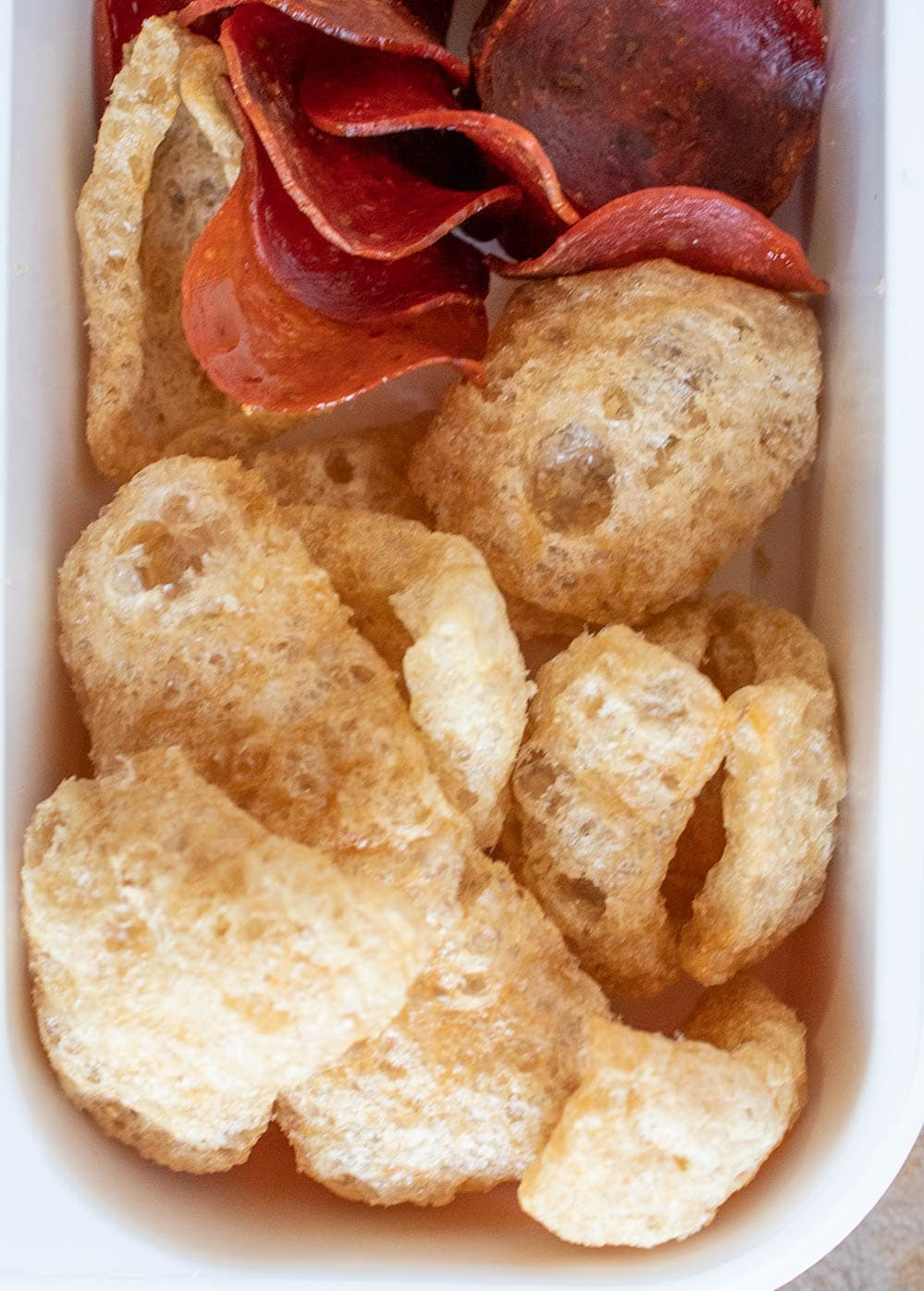 keto bistro box closeup containing pork rinds and pepperoni chips