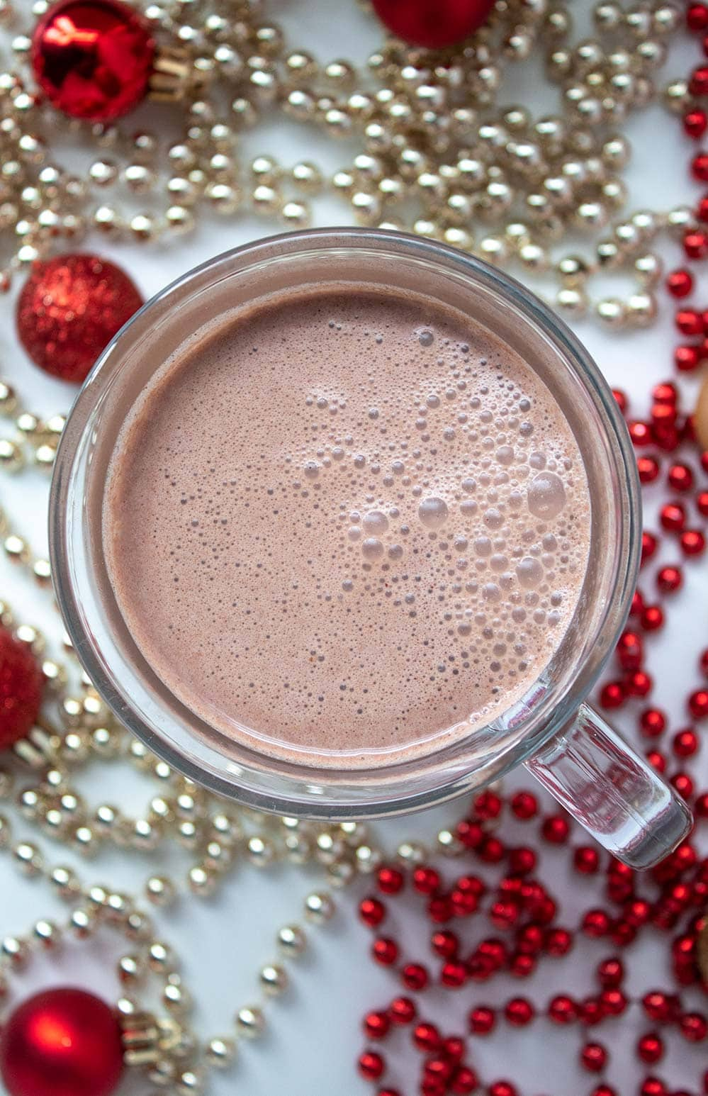 overhead view of keto peppermint mocha with red and gold decorative strings on ground