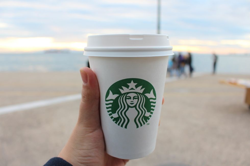keto starbucks cup in someone's hand held out in front of a scenic beach