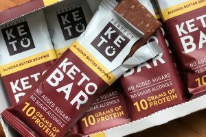 perfect keto bars review in a large box with open bar on top of other bars