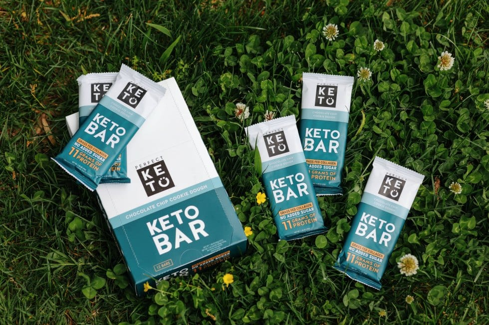 box of perfect keto bars review chocolate chip cookie dough bars on bright green grass in the spring