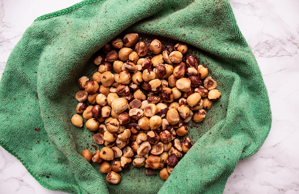 how to roast hazelnuts inside of a green cloth with skins partially rubbed off