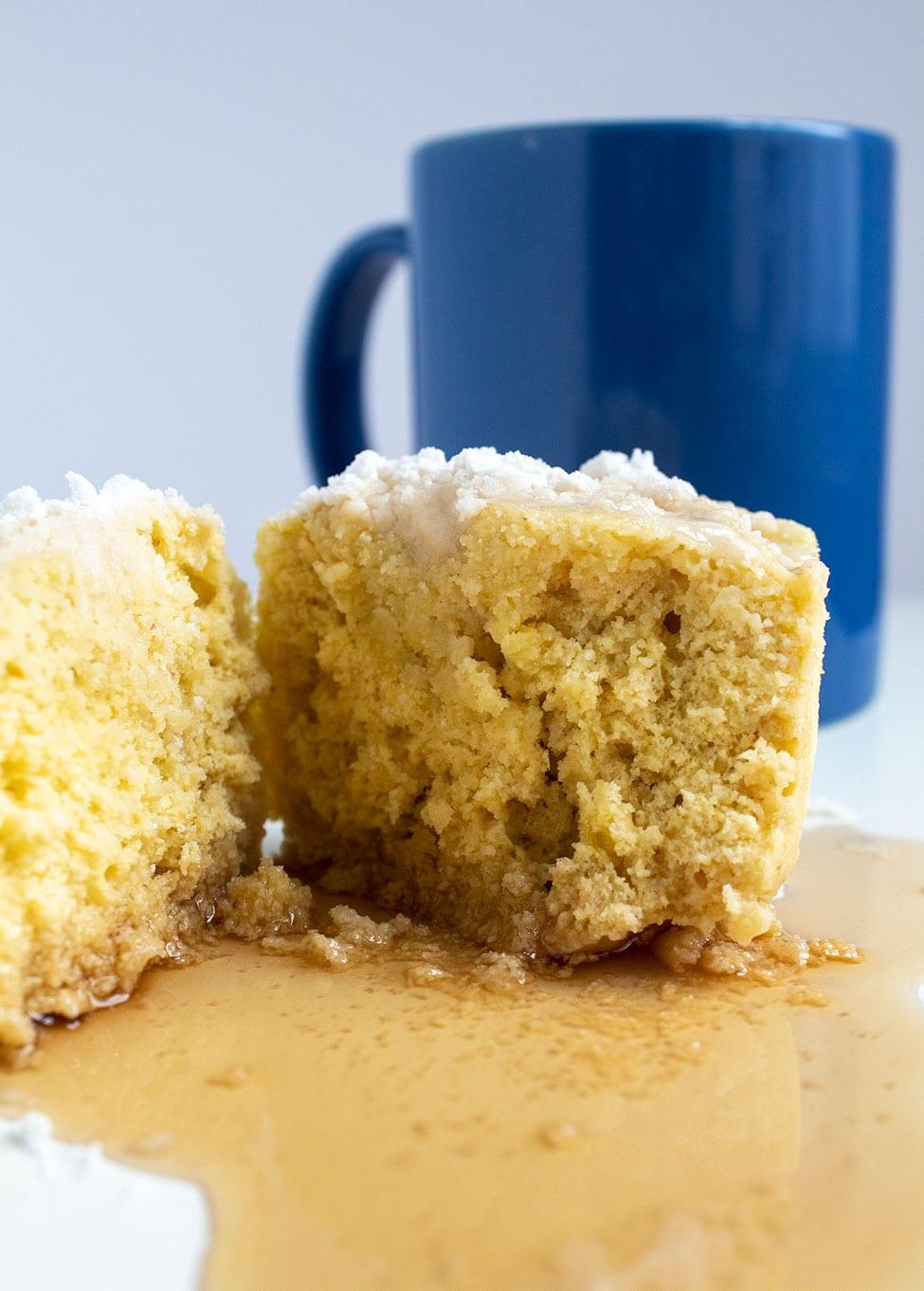 keto pancake mug cake in front of a blue mug with cake split in half
