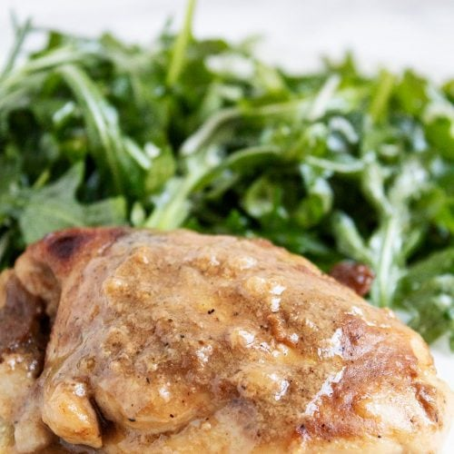 keto chicken thighs in front of a pile of seasoned arugula