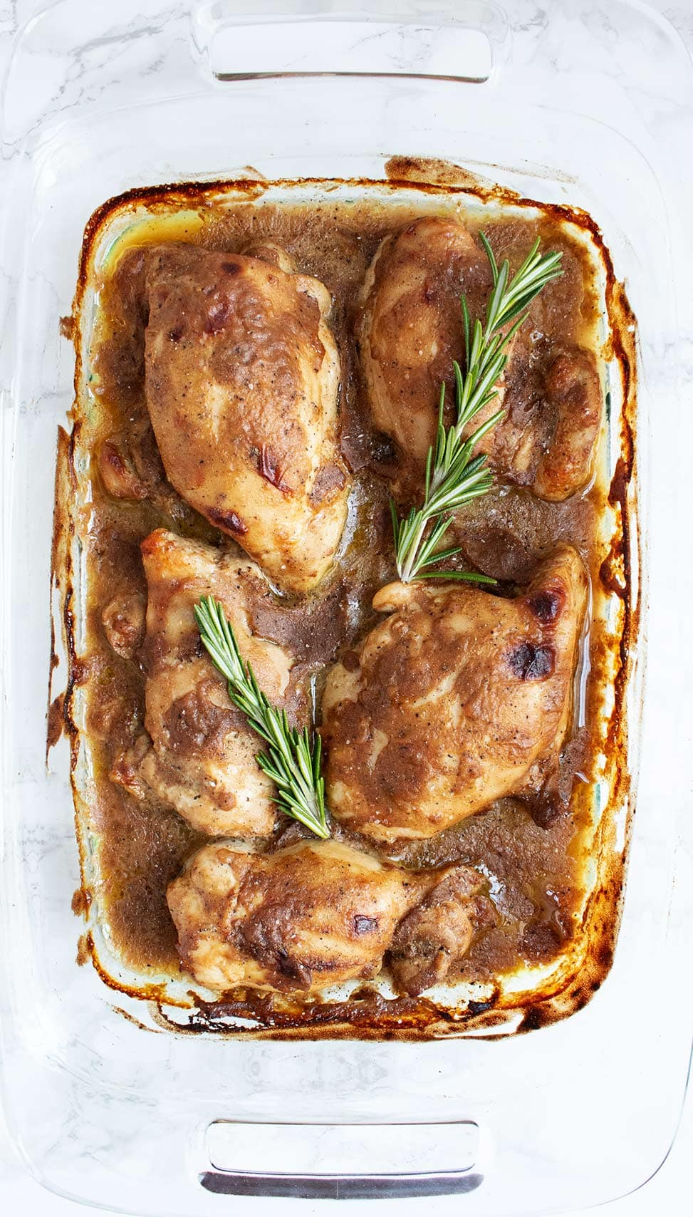 maple dijon keto chicken thighs fully cooked in a glass baking dish with rosemary on top