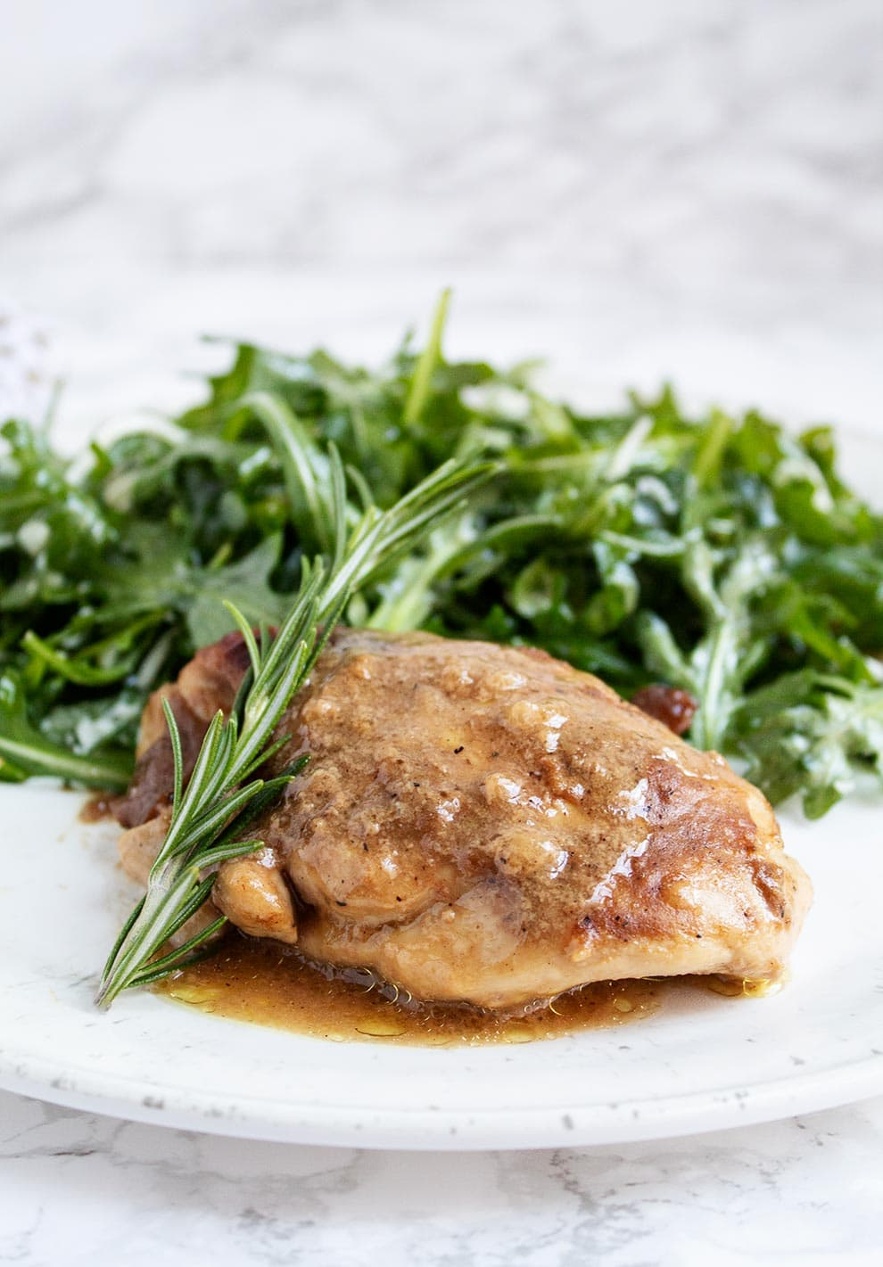 keto chicken thighs garnished with a rosemary sprig on a plate with arugula salad