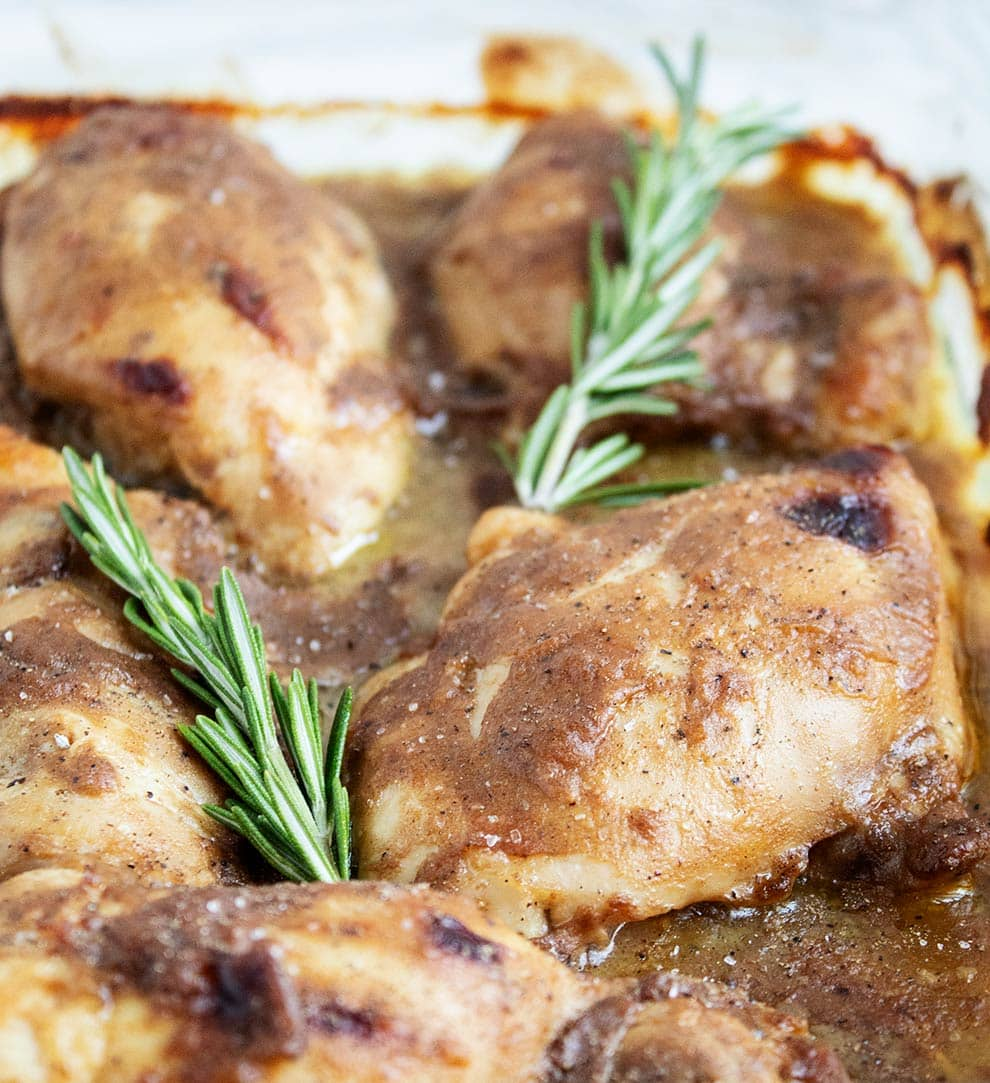 keto chicken thighs in a pan with two sprigs of fresh rosemary