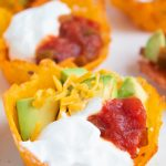 keto taco cups closeup with sour cream, avocado, cheese, and salsa