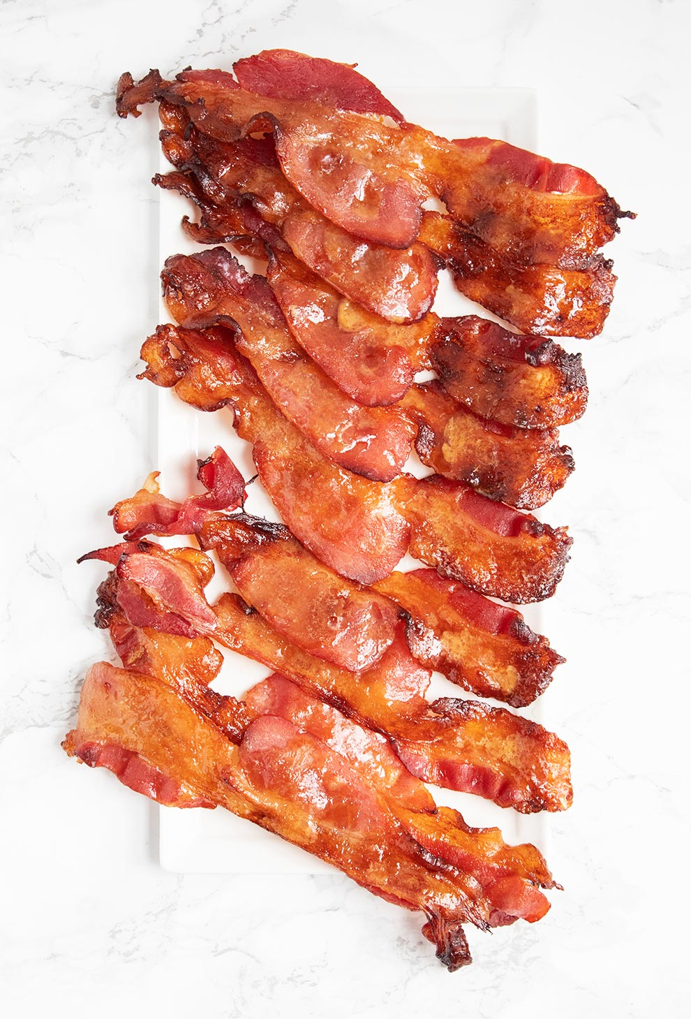 keto candied bacon laid down on a white plate in strips