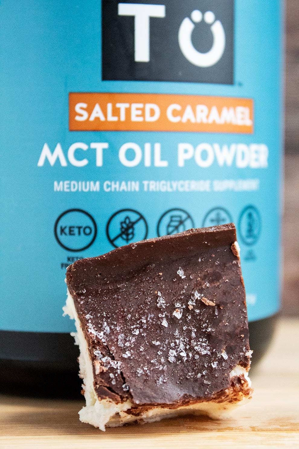 perfect keto salted caramel mct oil powder container next to keto salted caramel fat bomb bar