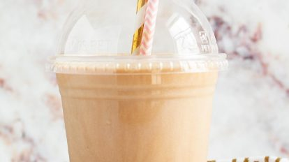 keto frappuccino keto iced coffee in a plastic cup with two decorative straws sticking out
