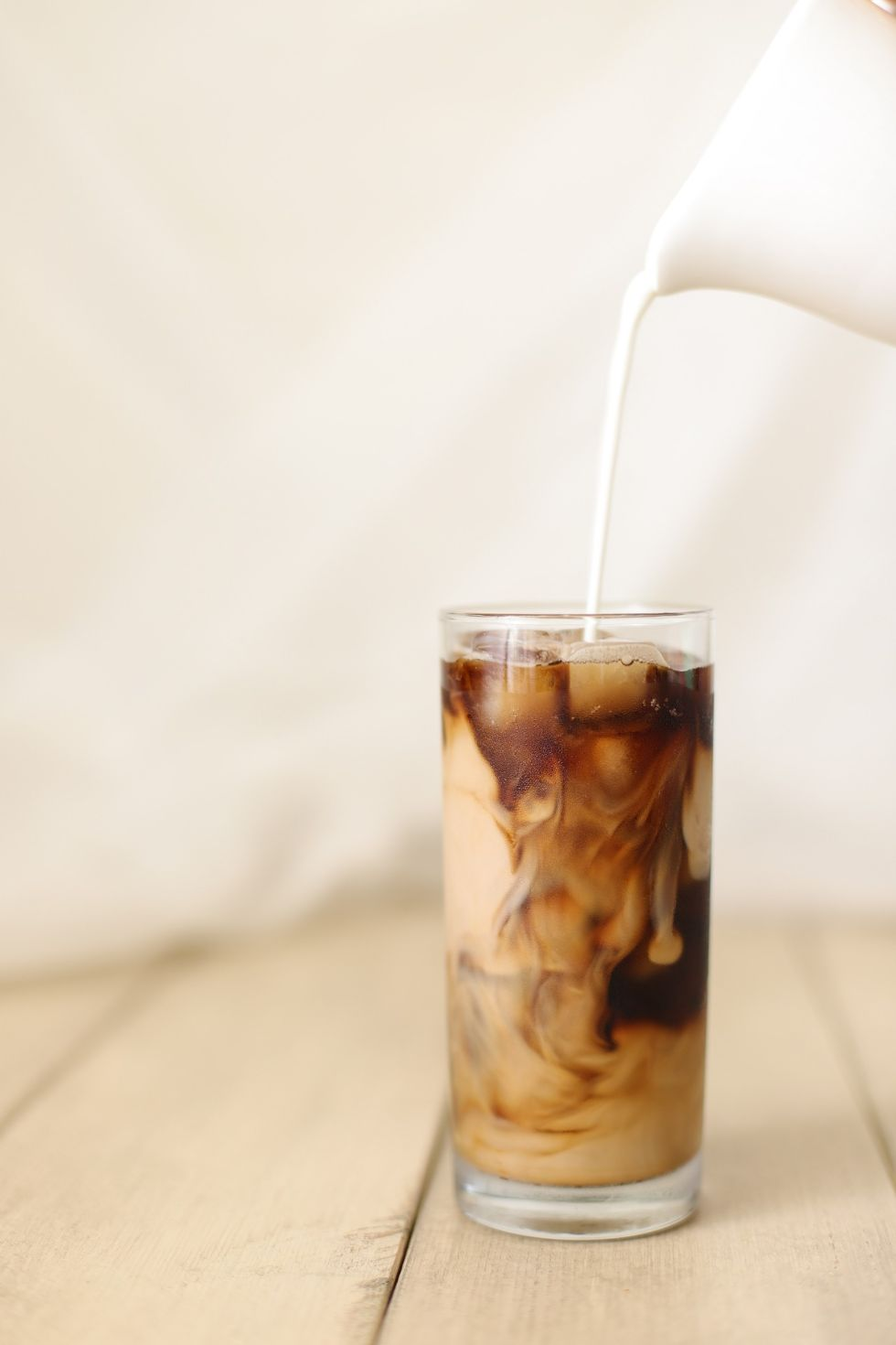 creamer being poured into a mason jar with keto iced coffee inside
