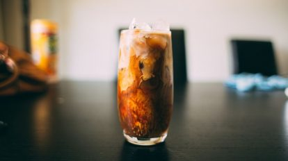 a glass of keto iced coffee sitting on a dark brown table